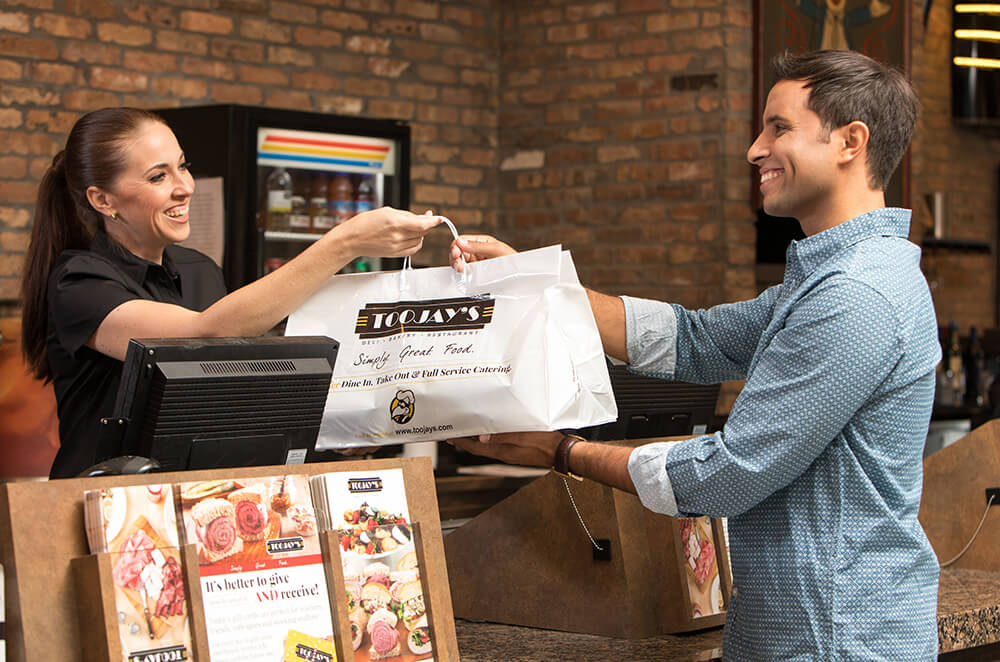 Man picking up to-go food from TooJay's
